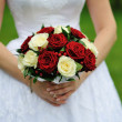 Bride holding wedding flower bouquet of red and white roses — Stock Photo
