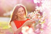 Krásná mladá žena v jarní zahradě poblíž kvetoucí strom — Stock fotografie