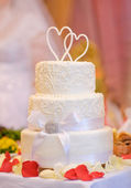 Multi-tiered white wedding cake with two hearts above — Stock Photo