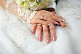 Hands of the groom and the bride with rings on a white dress — Stock Photo