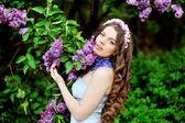 Portrét mladé ženy poblíž kvetoucí šeřík — Stock fotografie