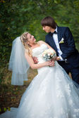 Elegante bruid en bruidegom poseren samen buitenshuis op een trouwdag — Stockfoto