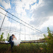 Groom and bride sitting on bridge — Stock Photo