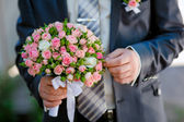 Groom is holding a wedding bouquet — Stock Photo