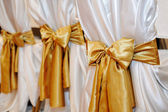 Wedding chairs in row decorated with golden color ribbon — Stock Photo