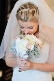 Bride holding white wedding bouquet of roses — Stock Photo