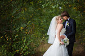 Bride and groom standing in the park — Stock Photo