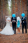Groom, bride and witnesses walking in autumn pine forest — Stock Photo