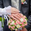 Hands of the bride and groom with rings on wedding bouquet — Stock Photo