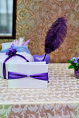 Beautiful wedding envelope with a purple ribbon and pen on the table — Stock Photo