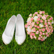 Wedding bouquet and shoes lying down on green grass — Stock Photo