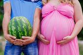 Vientre de un vientre embarazado y su esposo con una sandía — Foto de Stock