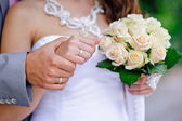 Hands and rings and wedding bouquet — Stock Photo