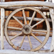 Old wood coach wheel around barn — Stock Photo