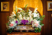 Wedding accessories and interior in Saint Trinity Orthodox Convent including two candlesticks with many candles, flowers, icons and Holy Bible. Wonderful church in Riga, Latvia — Stock Photo