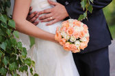 Hands of the groom and the bride on wedding bouquet — Stock Photo