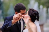 Bride and groom holding the ring in the foreground — Stock Photo