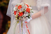 Bride holding a wedding bouquet with white and red flowers — Stock Photo
