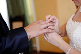 Bride putting a wedding ring on groom's finger — Stockfoto