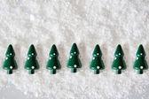 Miniature Christmas Trees on snow — Stock Photo