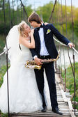 Bride and groom on the bridge with a saxophone — Foto Stock