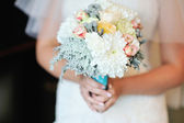 Wedding bouquet of white roses in bride's hands — Stock Photo