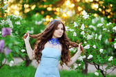 The beautiful woman with flowers of lilac — Stock Photo