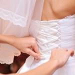 Bridesmaid tying bow on wedding dress — Stock Photo #38127625