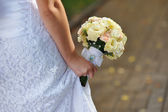 Bride holding white wedding bouquet — Stock Photo