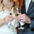 Closeup hands of the bride and groom with glasses of champagne — Stock Photo #38471429