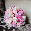 Wedding bouquet of pink roses lying on the sofa — Stock Photo #38471439