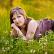 Beautiful woman enjoying daisy field, nice female lying down in — Stock Photo #39982963
