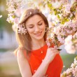 Young woman in red dress standing among blossom trees — Stock Photo #40014271