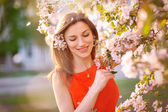 Young woman in red dress standing among blossom trees — Stock Photo