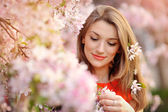 Portrait of beautiful woman near a flowering tree — Stock Photo
