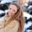 Beautiful girl on the street near fir-tree in winter — Stock Photo