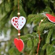 Beautiful decorations of hearts on a green Christmas tree — Stock Photo