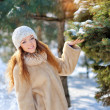 Pretty girl on the street near the Christmas tree in winter — Stock Photo