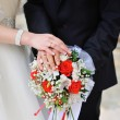 Stock Photo: Hands of the bride and groom with rings on a beautiful wedding bouquet