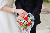 Hands of the bride and groom with rings on a beautiful wedding bouquet — Stok fotoğraf