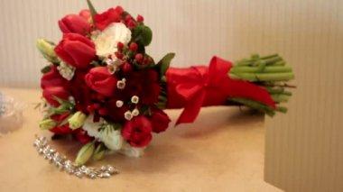 Bukiet ślubny z czerwonych róż i pierścienie na stole — Wideo stockowe