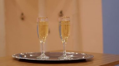 Two glasses with champagne standing on the table — Stock Video