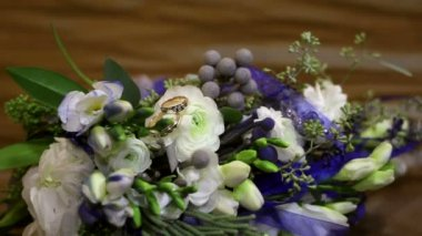 Gold rings lie on a beautiful bride's bouquet — Vídeo de Stock