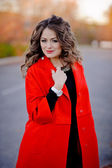 Beautiful girl in red coat standing on the road — Stock Photo