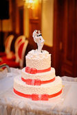 Three-tiered white wedding cake with red ribbons — Stock Photo