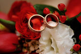 Gold wedding rings on a wedding bouquet close up — Stockfoto