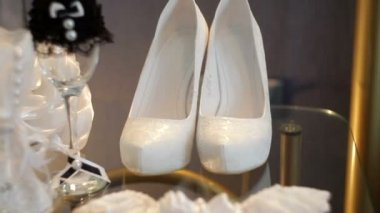White bridal shoes and wedding accessories on the table — Stock Video