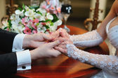 Groom holds his bride's hand — Stock Photo