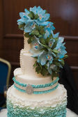 Beautiful turquoise three-tiered wedding cake with flowers on top — Stock Photo