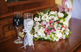 Beautiful wedding bouquet and two glasses with champagne — Stock Photo